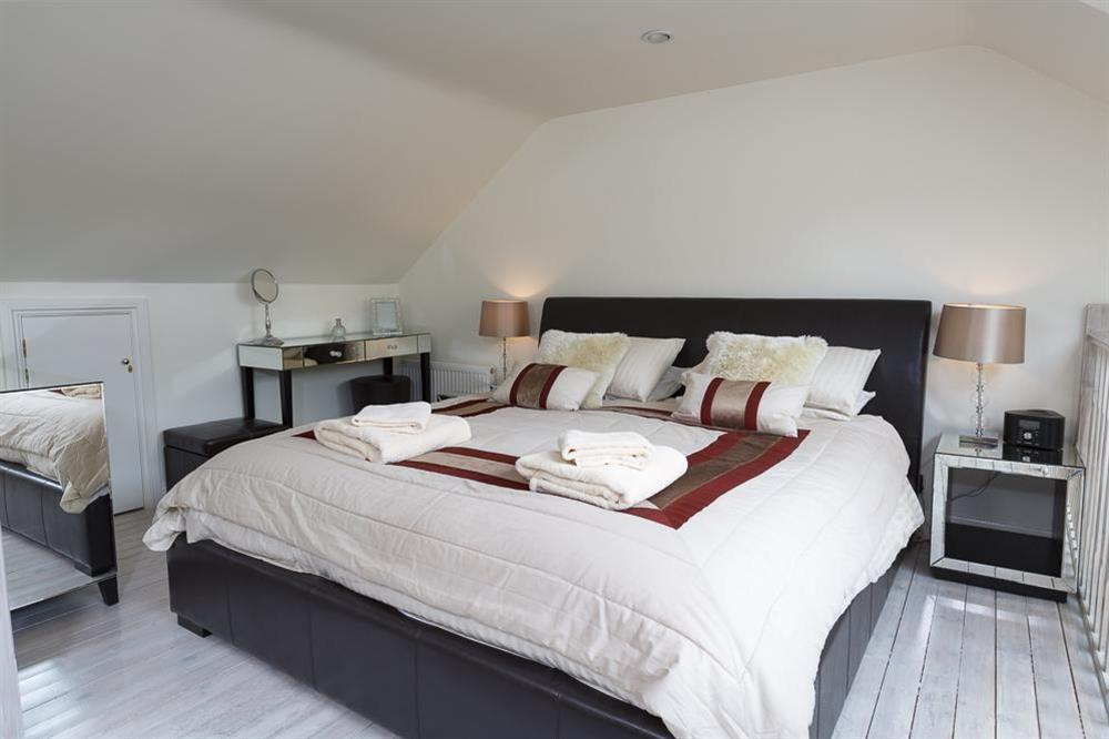 Bedroom with super-King size bed situated on a gallery above the living room at 16 Dartmouth House in , Dartmouth