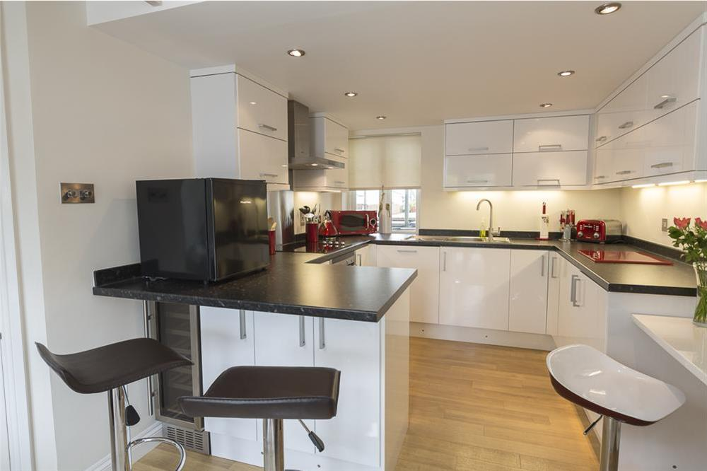 Kitchen area with breakfast bar with two stools at 16 Dartmouth House in , Dartmouth