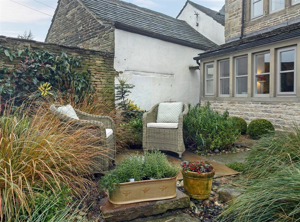 Small courtyard garden with sitting-out area at 3 Healey Cottage in Shelley, near Huddersfield, West Yorkshire