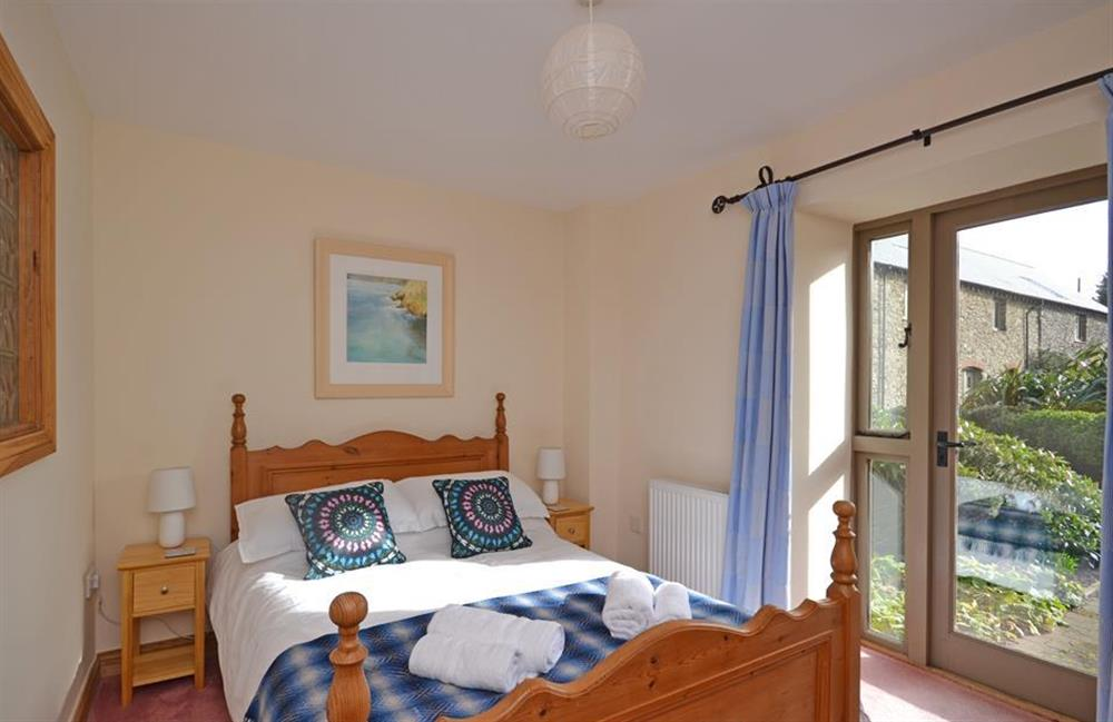 The double bedroom with doors leading outside at 5 West Hartley Barns, Blackawton
