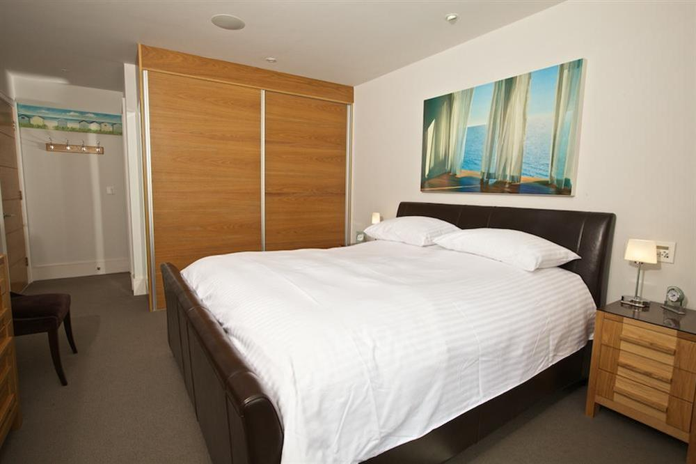 Master bedroom with leather-framed double bed at 7 Dart Marina in Sandquay Road, Dartmouth