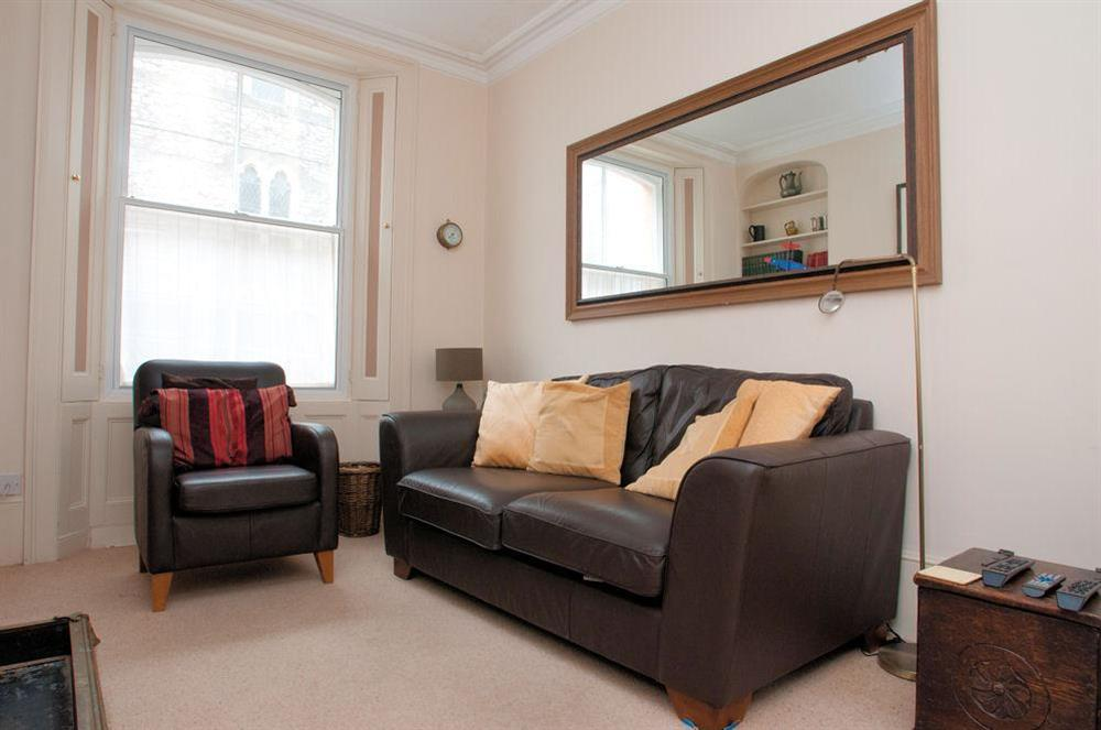 Sitting room with leather sofa and chair at Aeolus House in 42 Newcomen Road, Dartmouth