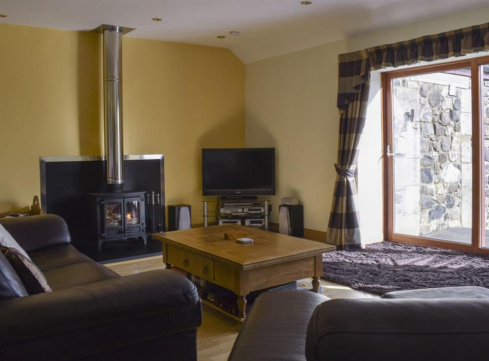 Well presented living room with wood burner at The Byre,