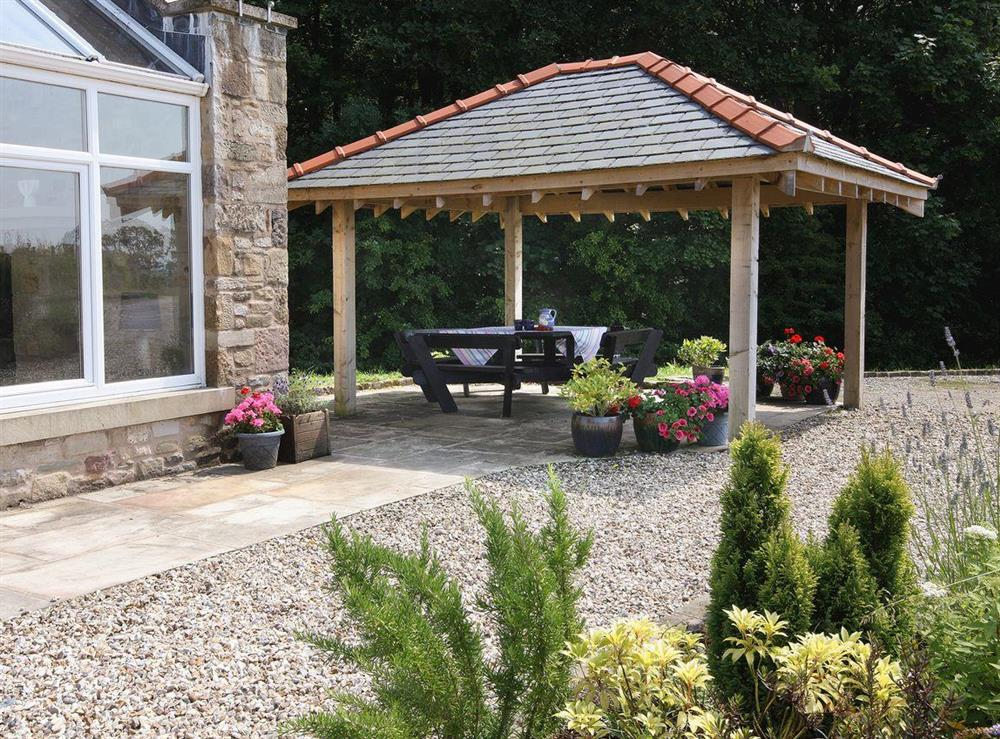 Patio with outdoor seating under the sturdy gazebo at Woodpecker Cottage,
