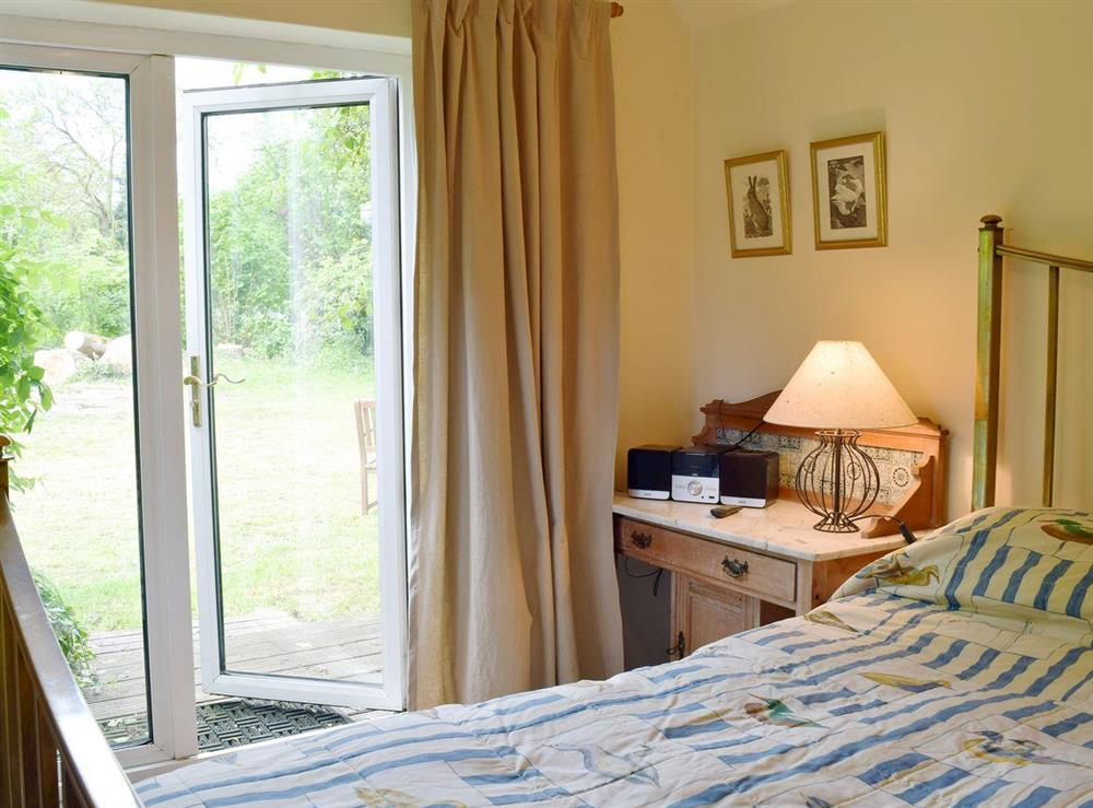 Double bedroom with patio doors opening to the orchard at Beck Gate in Denton, near Bungay, Norfolk