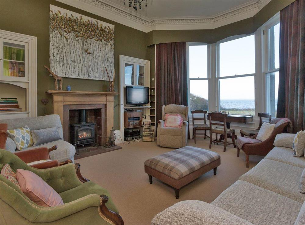 Living room with wood burner and great sea views from the bay window at Bentfield in Prestwick, Ayrshire