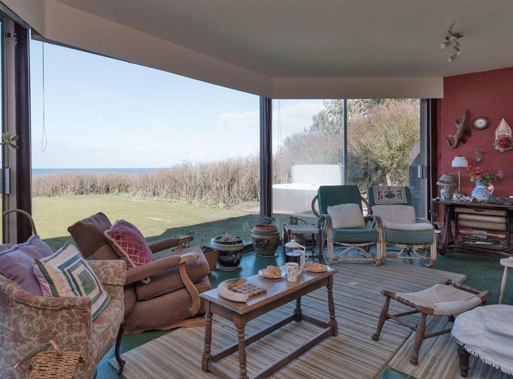 Sun room with patio doors that lead onto the garden at Bentfield in Prestwick, Ayrshire