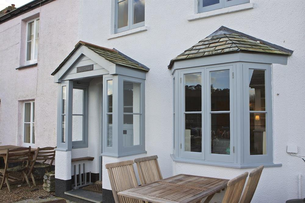 Table and chairs on the quayside at the front of the cottage at Berry Cottage in , Dittisham