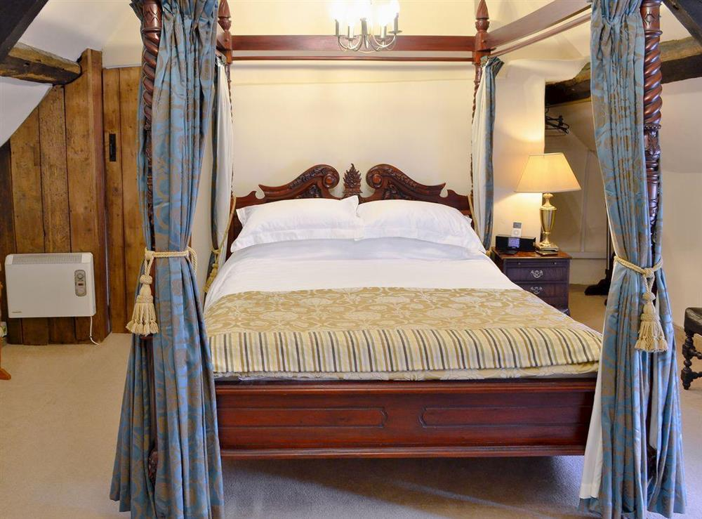 Large bedroom with ornate four-poster bed at Betsy Cottage in Butleigh, near Glastonbury, Somerset