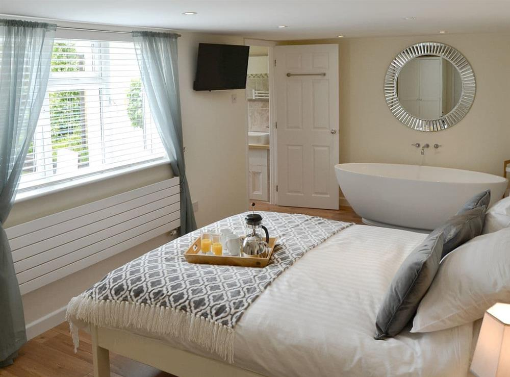 Attractive master bedroom with free standing bath at Broadland Hideaway in Martham, near Great Yarmouth, Norfolk