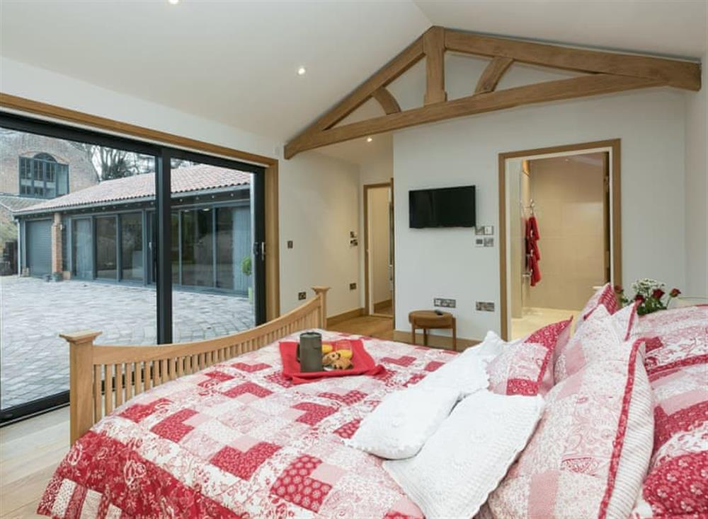Double bedroom with bi-folding doors at Bumblebee Cottage in Geldeston, near Beccles, Norfolk