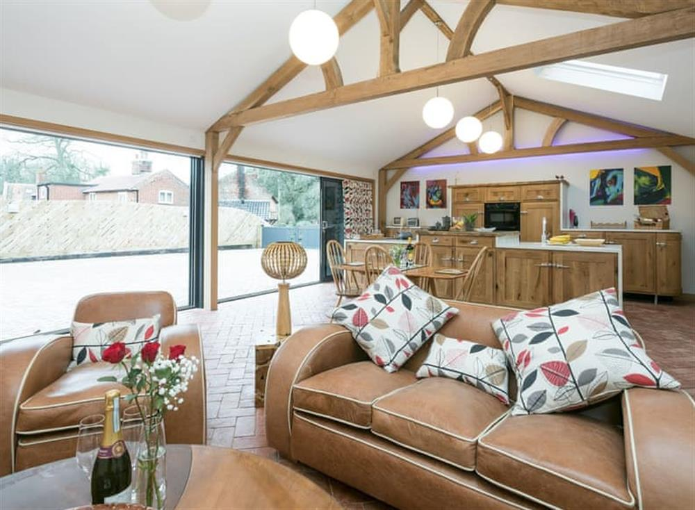 Open plan living space with bi-folding doors leading to garden at Bumblebee Cottage in Geldeston, near Beccles, Norfolk