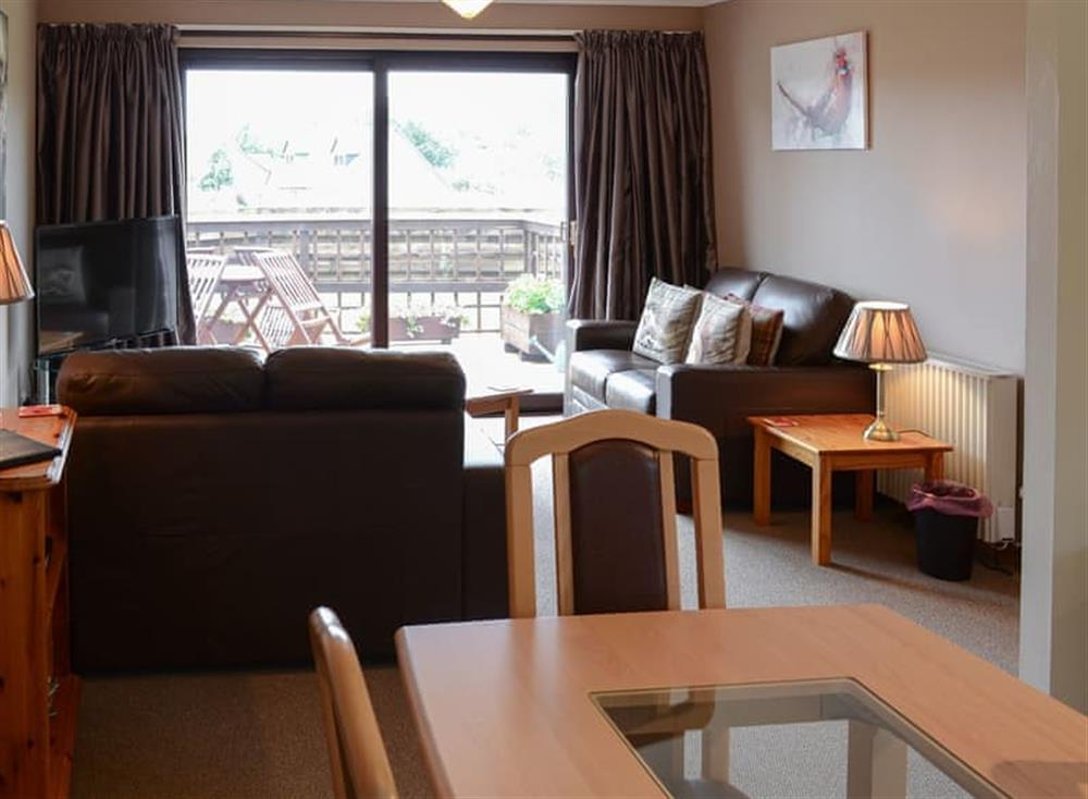 Living room with dining area at Burn Cottage in Lairg, near Golspie, Sutherland