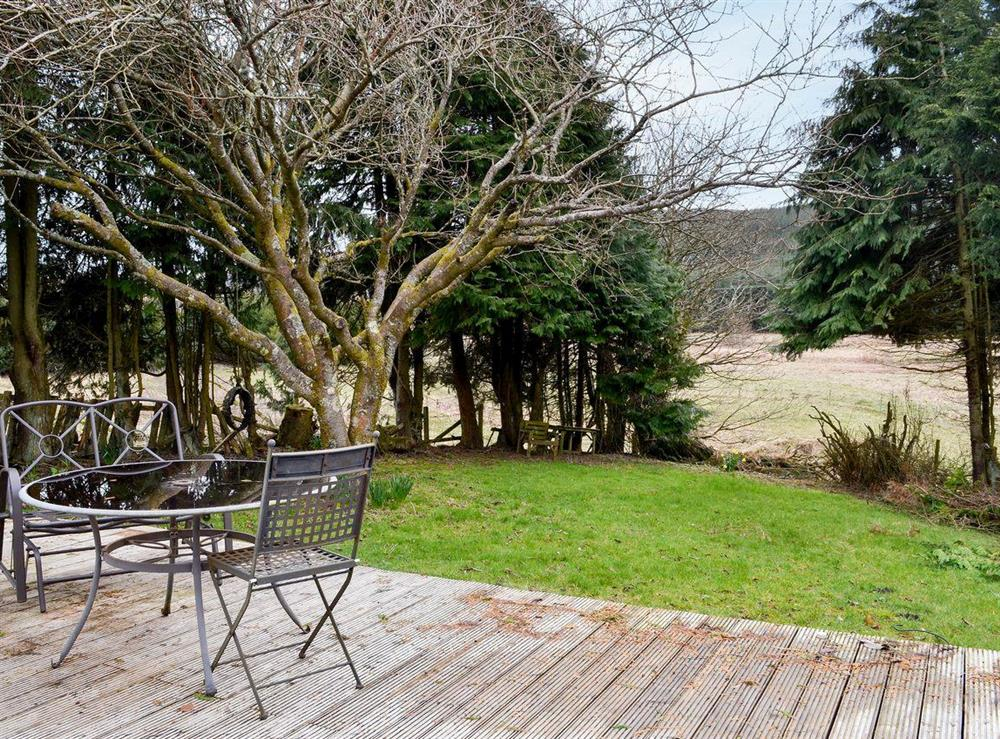 Enclosed lawned garden with sitting-out area and garden furniture at Burnside Cottage in Tormitchell, near Girvan, Ayrshire