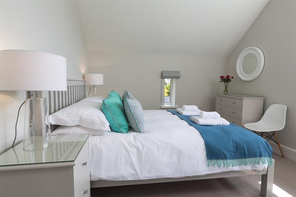 En suite master bedroom with King-size bed at Carriage Loft Cottage in Hillfield, Dartmouth