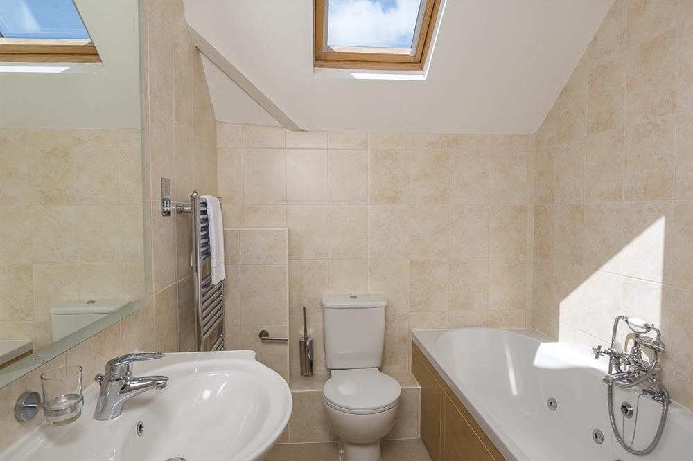 Family bathroom with whirlpool bath at Carriage Loft Cottage in Hillfield, Dartmouth