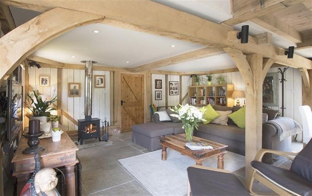 Ground floor: Open plan sitting room with wood burning stove at Cherrystone Barn, Ripe