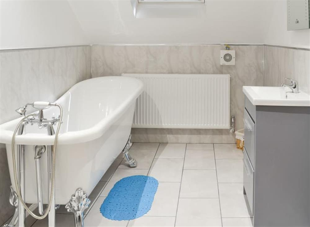 Bathroom with telephone-style shower attachment on the bath at Christine Cottage in Flamborough, North Humberside
