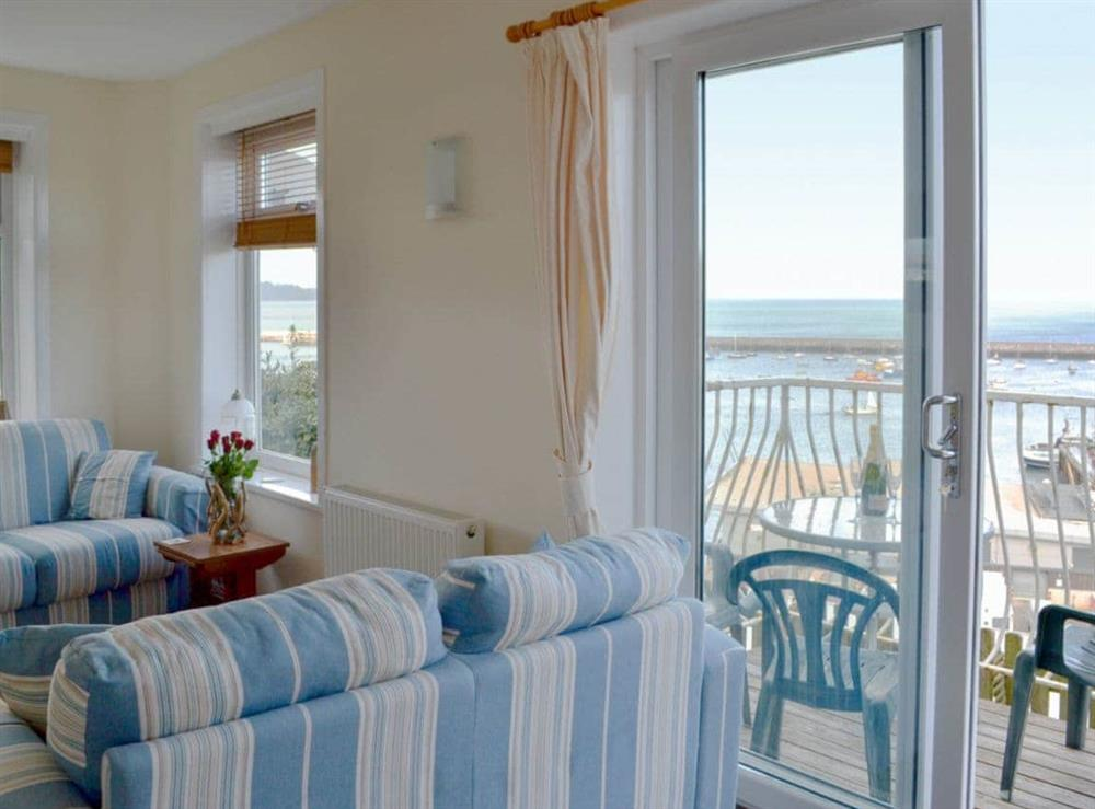 Cosy living room with direct access to balcony at Cliff Cottage in Brixham, Devon