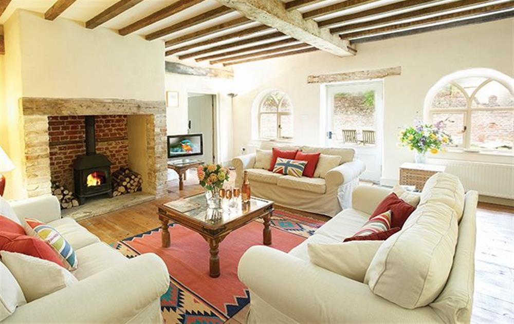 Ground floor: Sitting room with inglenook fireplace and wood burner at Coach House (Norfolk), Banningham