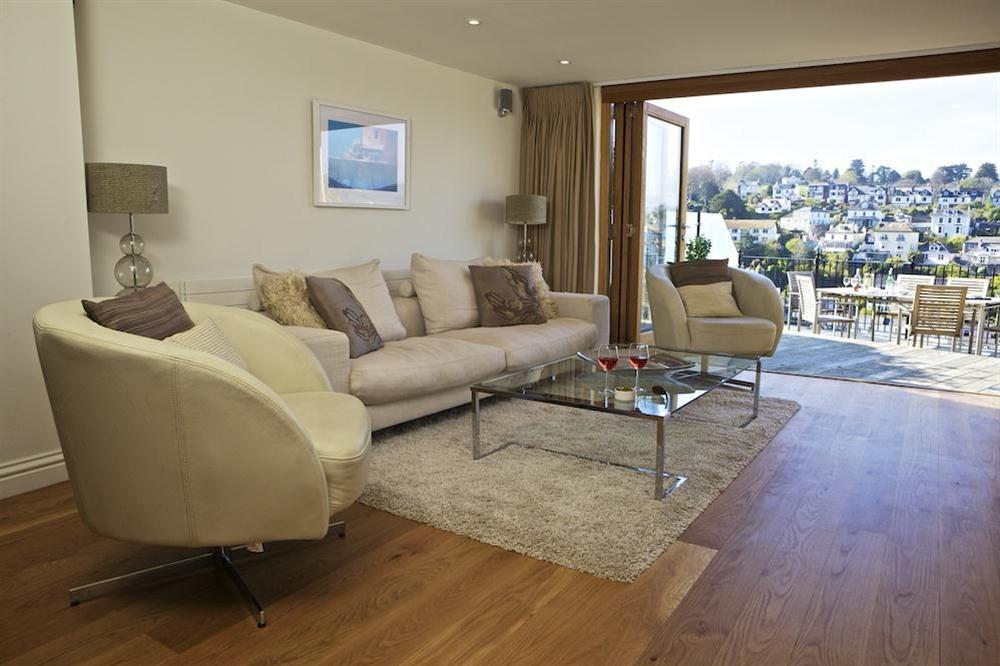 Tastefully furnished lounge area with doors out to terraced balcony at Cobbs Cottage in 20 Crowthers Hill, Dartmouth