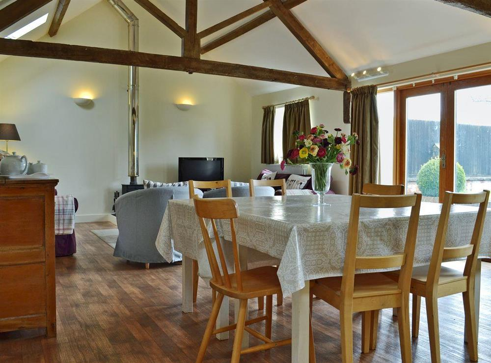 Stylishly furnished open plan living space with beams at The Burrow,