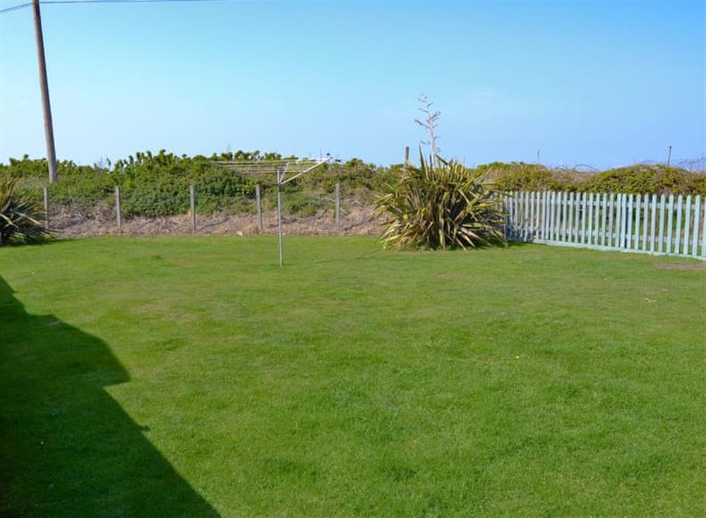 Large lawned garden at Cottage By The Sea in Bacton, near North Walsham, Norfolk