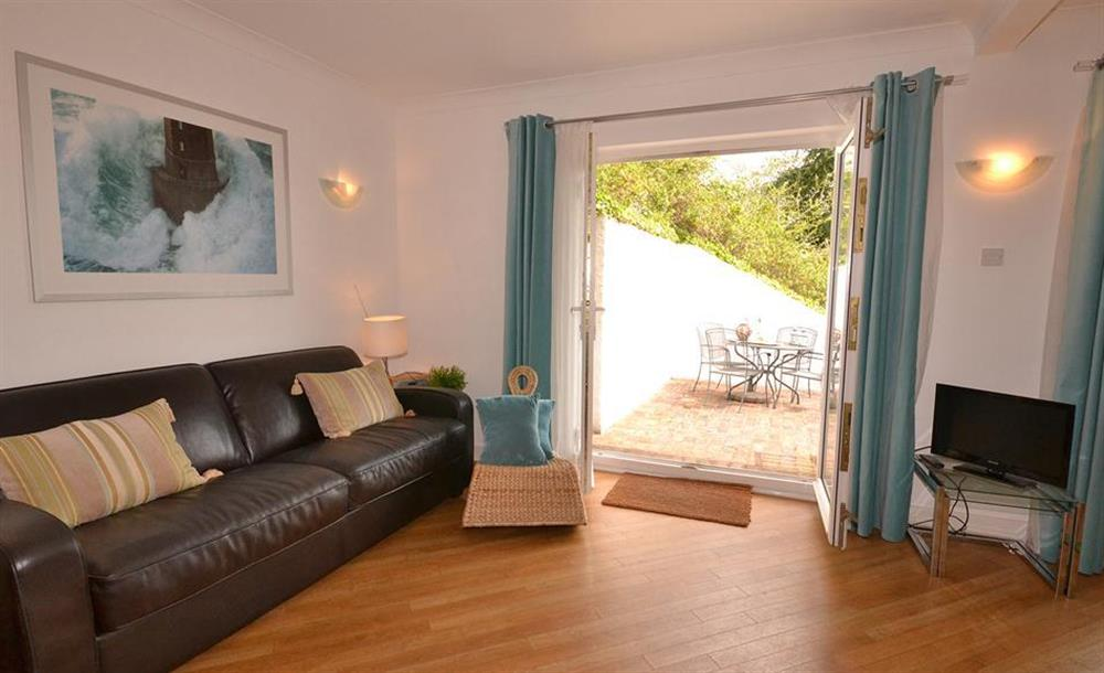 A comfortable sofa in the kitchen diner and doors to lower terrace at Cotterbury, Dartmouth