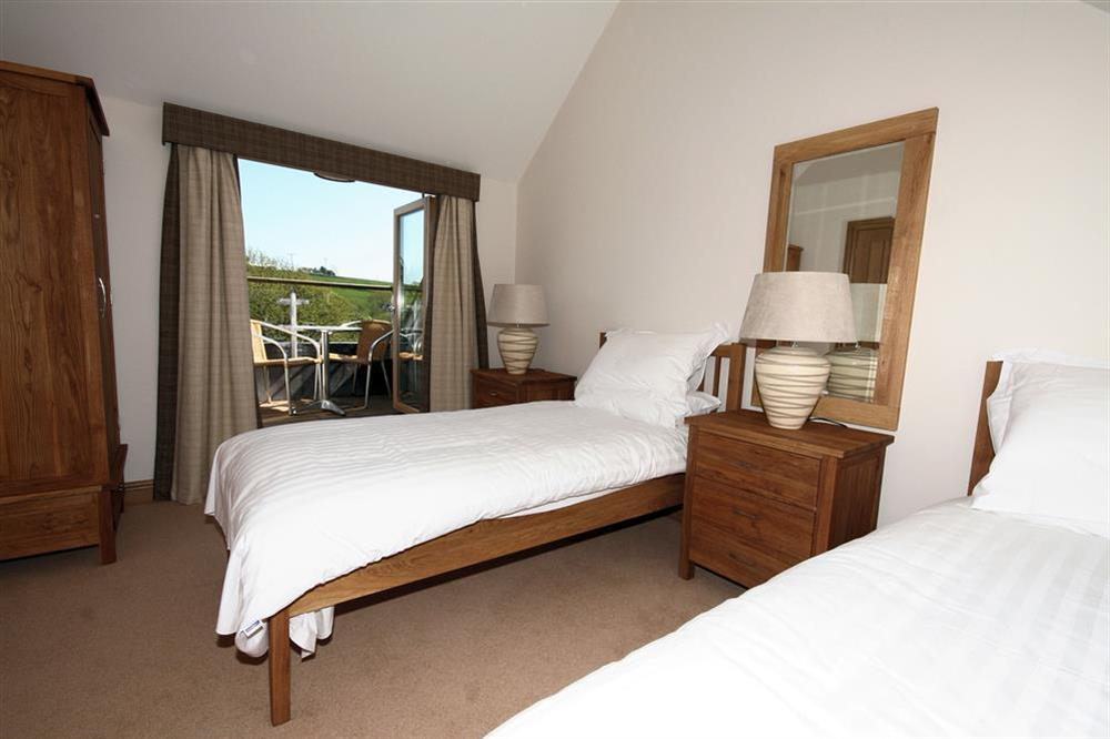 Twin bedroom with french doors leading to balcony at Court Cottages 1 in Hillfield, Dartmouth