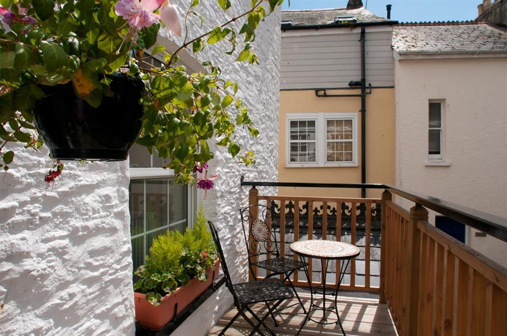 Decked balcony overlooking the courtyard, with table and four chairs at Courtyard House in , Dartmouth