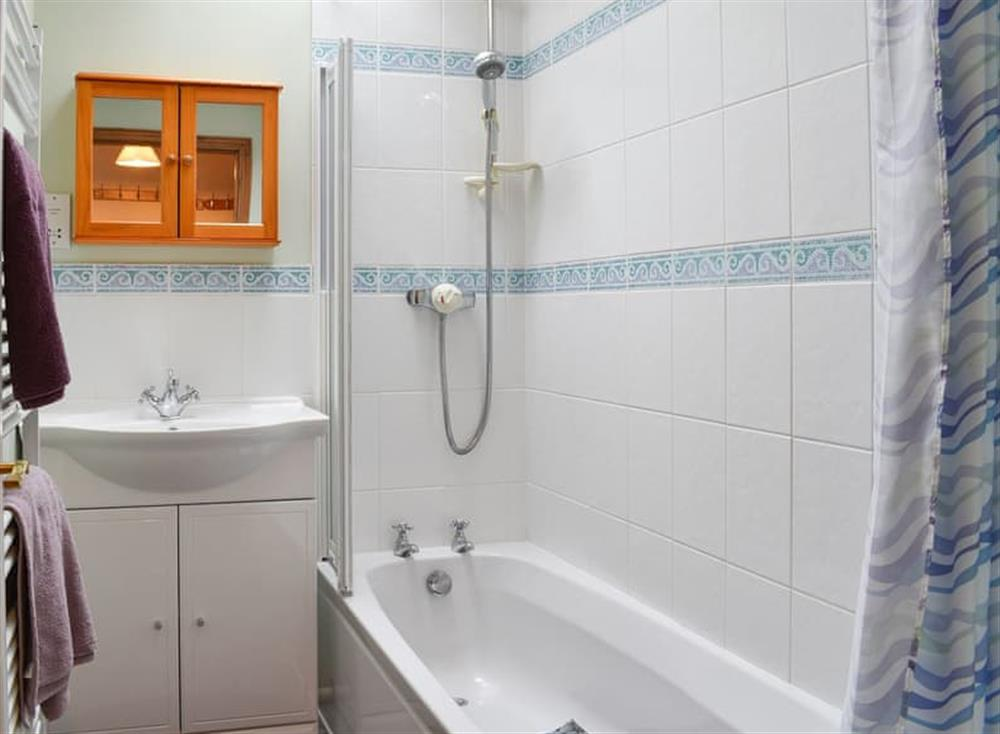 Pretty tiled bathroom with shower over the bath at Croft Cottage in Lydlinch, near Sturminster Newton, Dorset