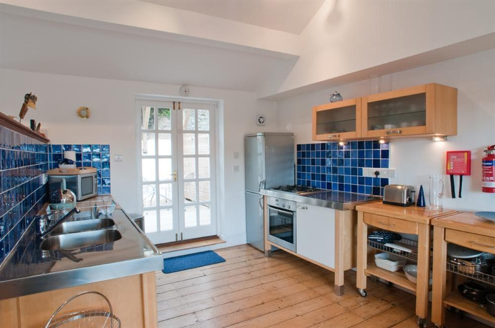 Kitchen with patio doors leading to decking at rear of property at Dart Views in 98 Above Town, Dartmouth