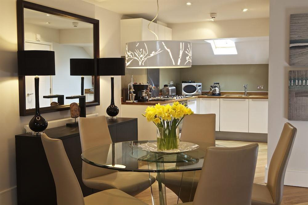 Stylish dining area with glass table and four chairs at Diddly Squat, 43 Dart Marina in , Dart Marina
