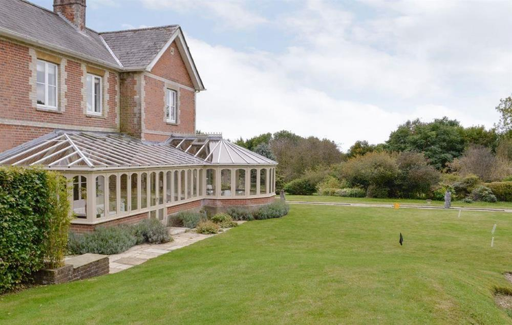 Rear view of the house, conservatory and croquet lawn