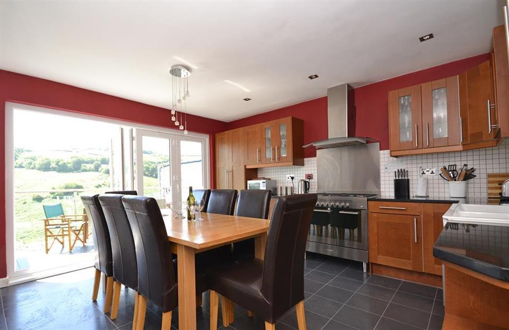 The modern kitchen diner with fully folding patio doors leading out to the top balcony at Driftwood, Dartmouth