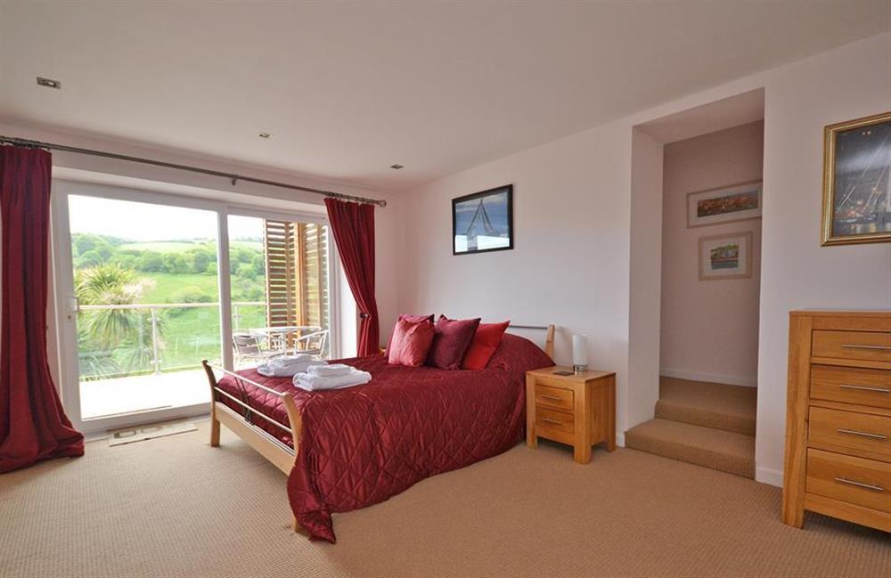The spacious master bedroom with patio doors leading out to the decked terrace at Driftwood, Dartmouth
