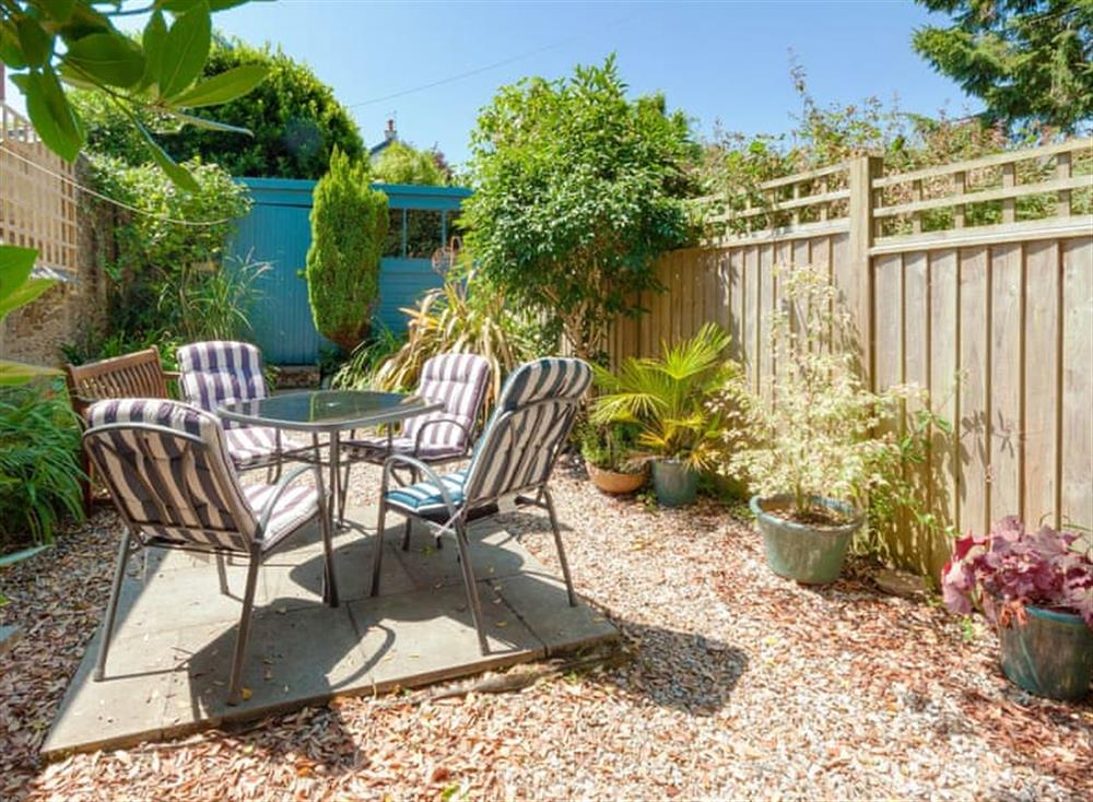 Pretty and secluded garden, with gravelled sitting area, outdoor furniture and BBQ at Driftwood in Stoke Fleming, Devon