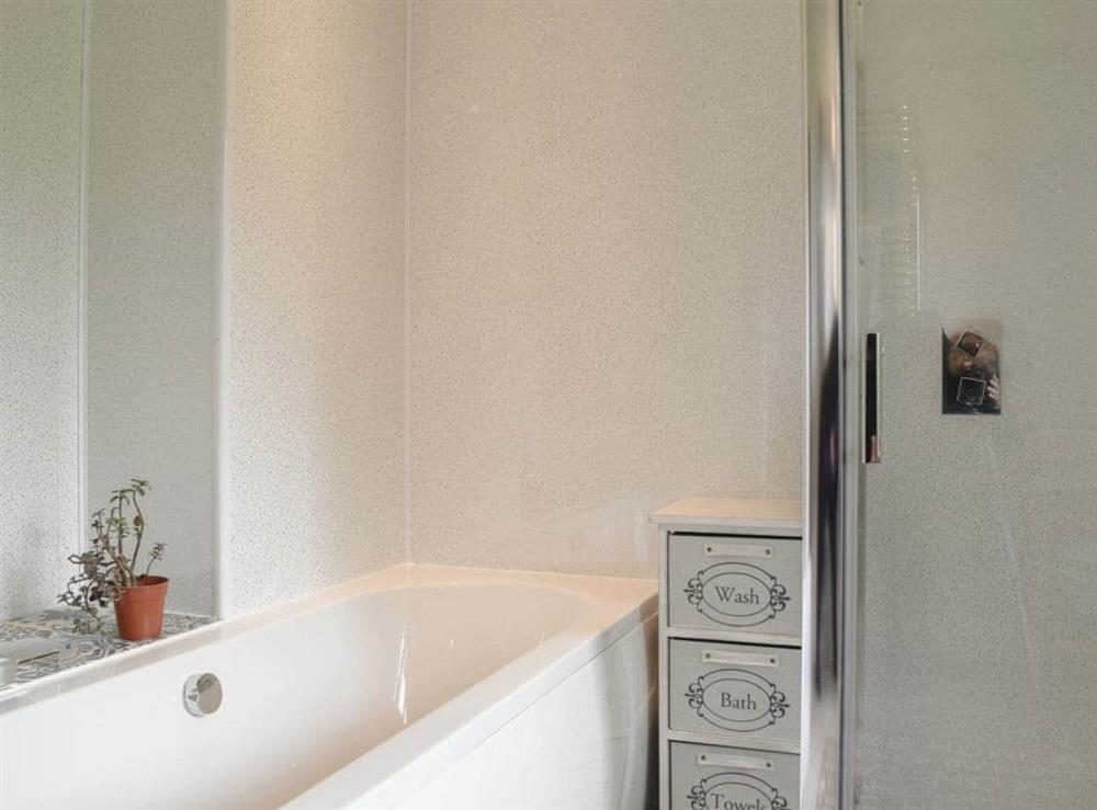 Bathroom with bath, shower cubicle, toilet and heated towel rail at Elm Cottage in Falkirk, Stirlingshire