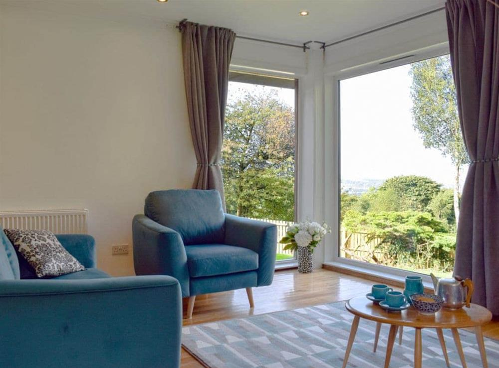 Comfy living area with large windows looking out to the countryside at Elm Cottage in Falkirk, Stirlingshire