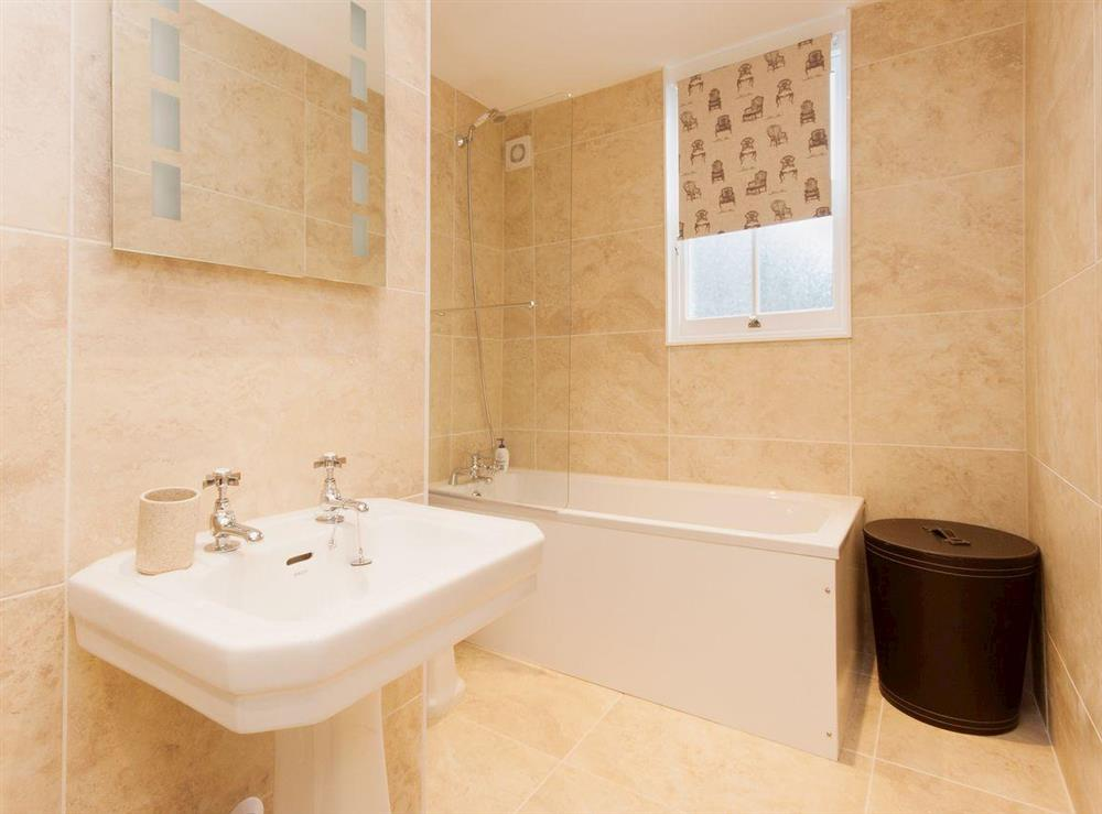 A large fully tiled family bathroom with over bath shower at Elm Grove in Dartmouth, Devon
