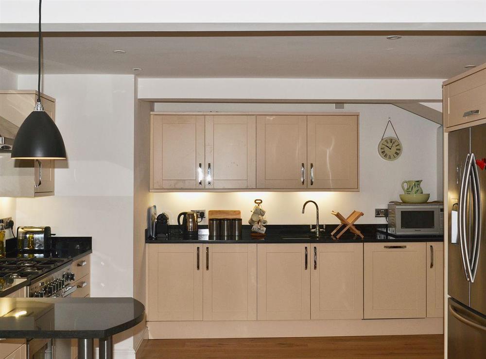Granite worktops and a stylish breakfast bar complete the modern kitchen at Elm Grove in Dartmouth, Devon
