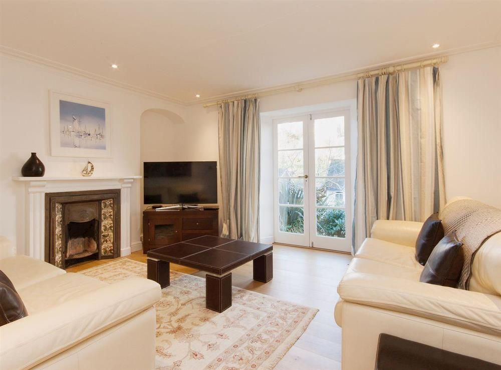 Lovely living room with feature fireplace, wooden floors and satellite television at Elm Grove in Dartmouth, Devon