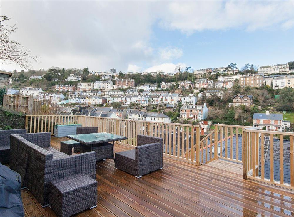 The decked area has modern patio furniture at which you can sit and have an al fresco meal whilst overlooking the town at Elm Grove in Dartmouth, Devon