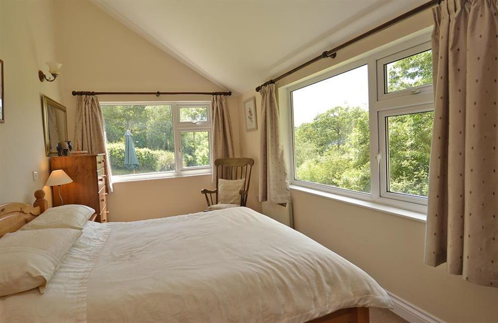 The lower ground floor bedroom with two large windows overlooking the garden at End O Moor, Shaugh Prior