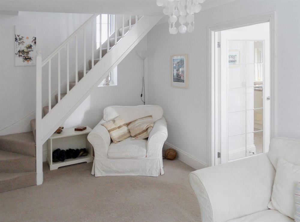 Living room with open staircase to firsrt floor at Evelyn Cottage in Dartmouth, Devon