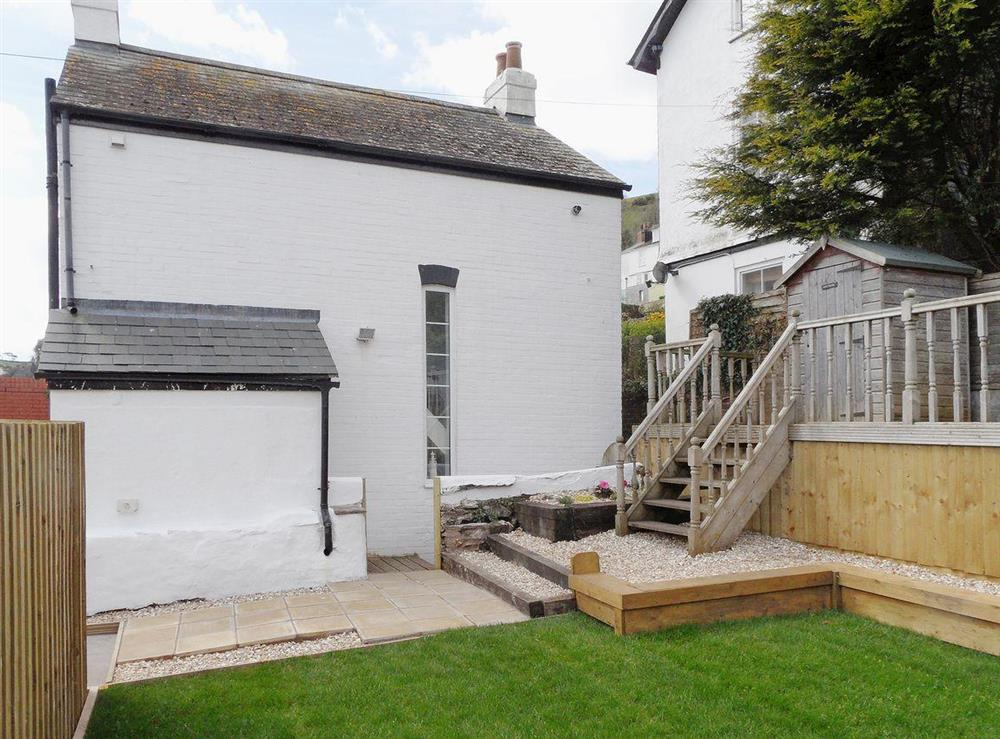 Whitewashed exterior with decking in the garden at Evelyn Cottage in Dartmouth, Devon