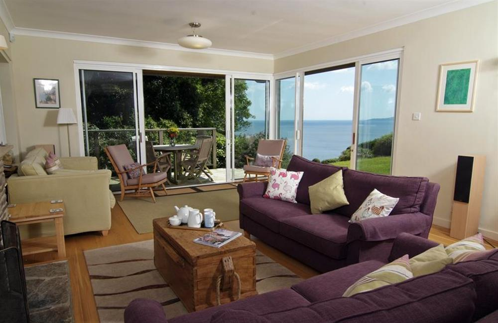 The living room with patio doors that open onto the decking and sea views at Fairyfield, Stoke Fleming