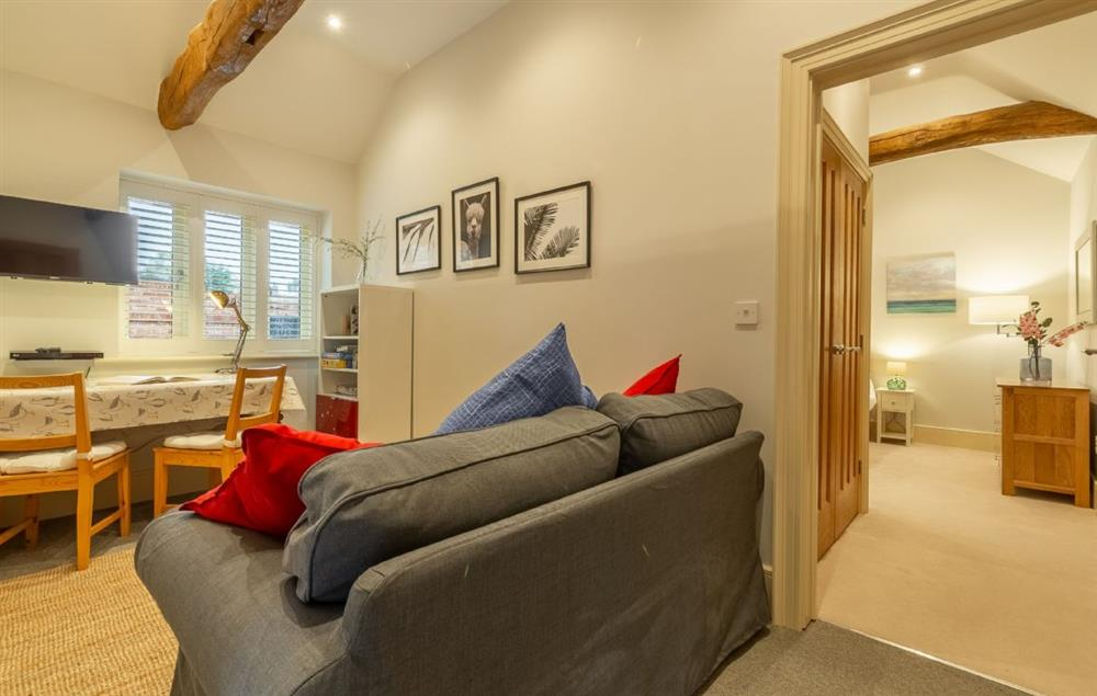 Ground floor: Snug vaulted room with beams, sofa, TV, DVD player and table