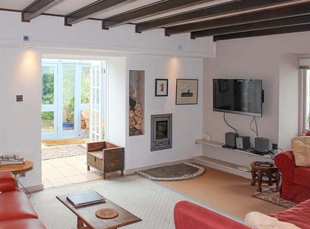 Spacious living room with wall-mounted log burner at Upper Mill,