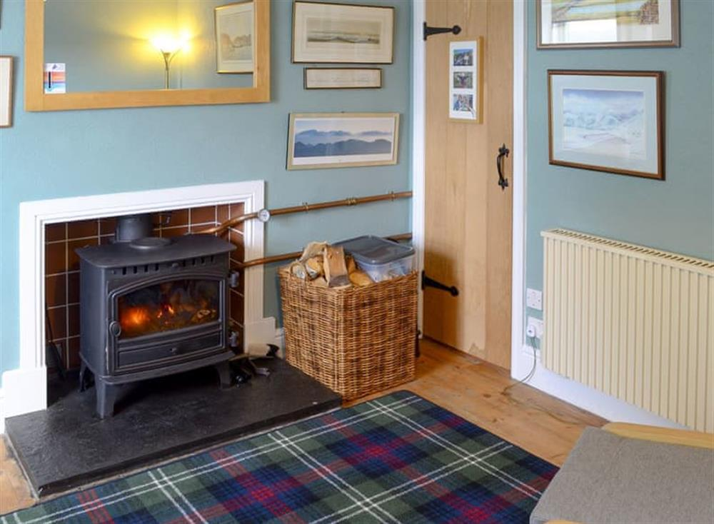 Warm, welcoming living room with large wood burner at Gairs Cottage in Bonar Bridge, near Tain, Ross-Shire